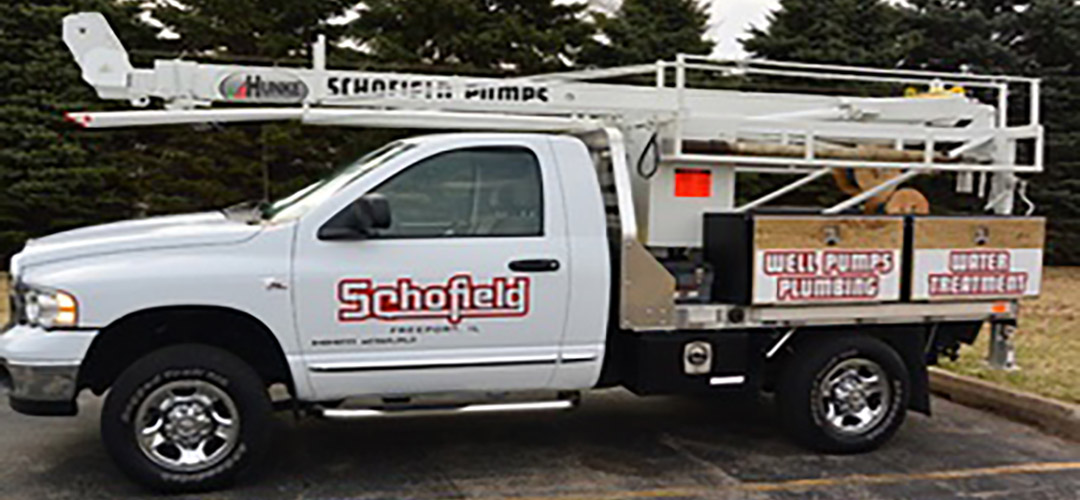A white Schofield truck with a well drilling rig installed.