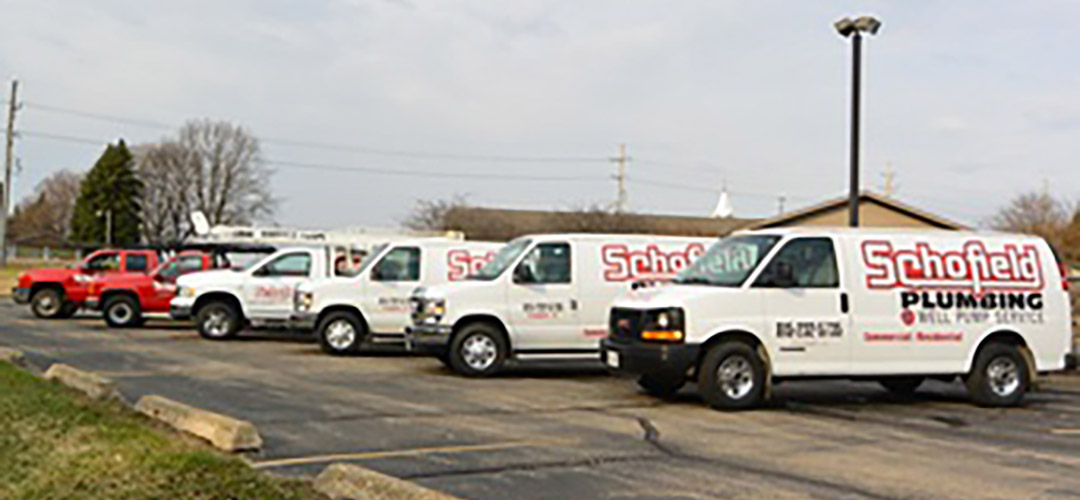 A row of six red and white Schofield trucks, ready to provide plumbing service or well service to customers throughout the Freeport area.